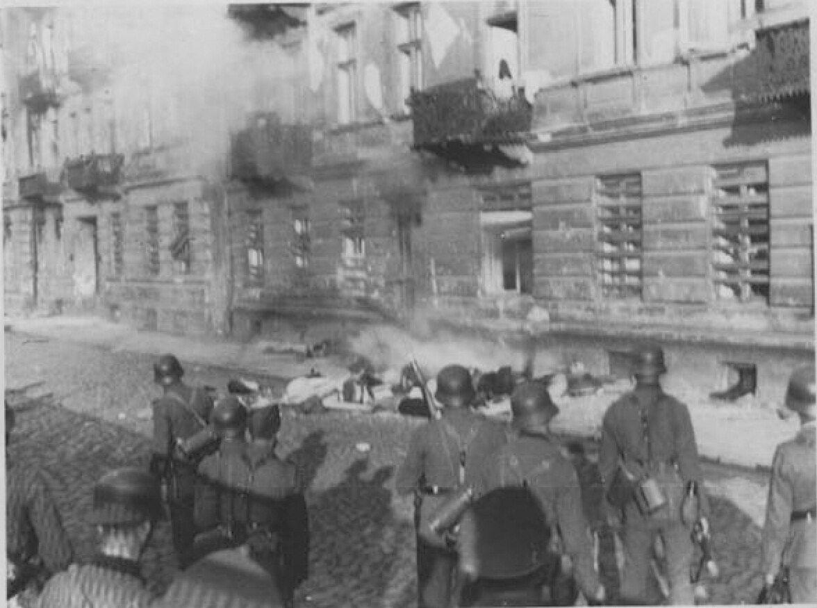 """SS-mani stoją nad zwłokami Żydów, którzy popełnili samobójstwo wyskakując kamienicy, by nie dostać się w ręce Niemców. Oryginalny napis z raportu gen. Stroopa: """"Bandyci, którzy wyskoczyli""""."""
