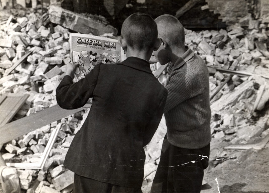 Dzieci w oblężonej Warszawie Dwóch chłopców z niedzielnym dodatkiem gazety na gruzach zburzonych budynków. Fotografia Juliena Bryana.